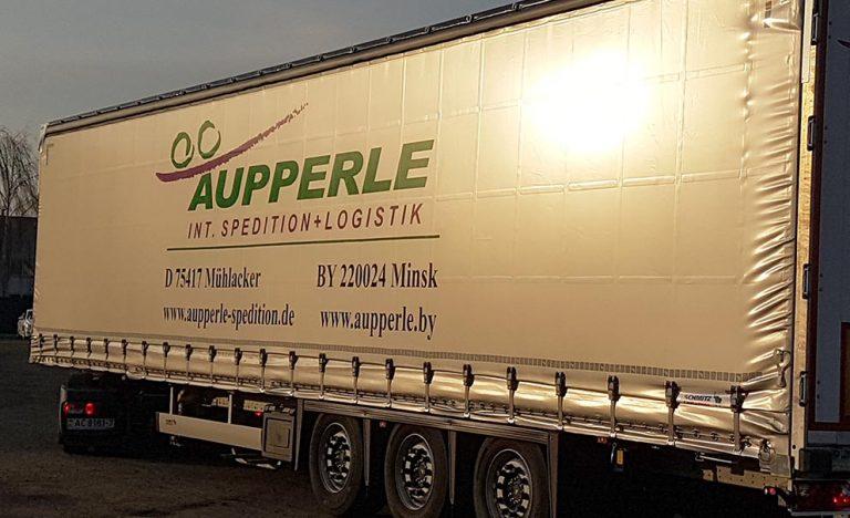 Sonne spiegelt sich auf der Plane eines LKW der Firma Aupperle